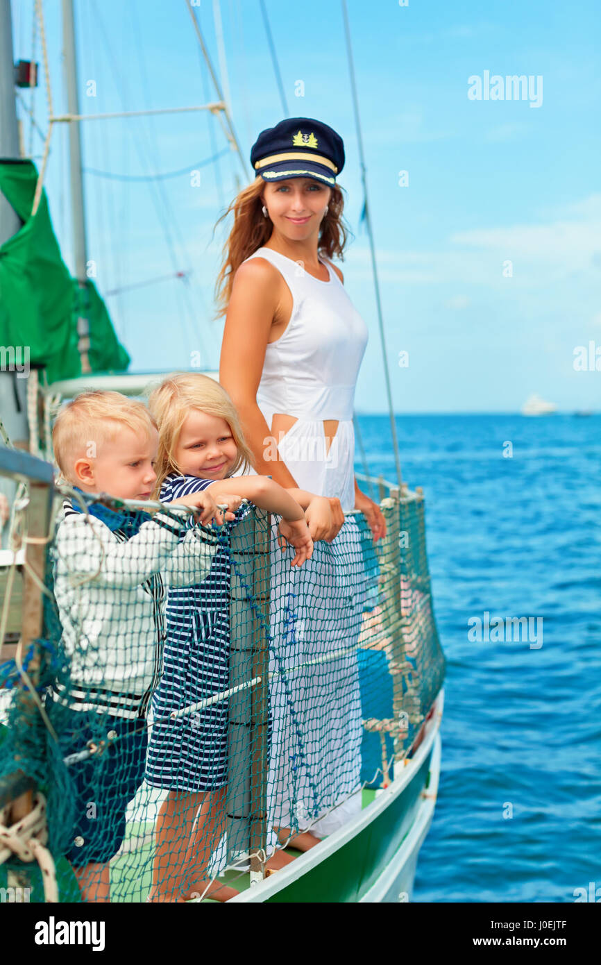 Happy family - mother in captain cap, baby son, daughter on board of sailing yacht. Children have fun discovering - Stock Image