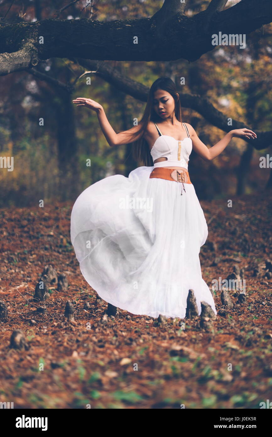 Beautiful wiccan girl dancing in the mystical forest - Stock Image