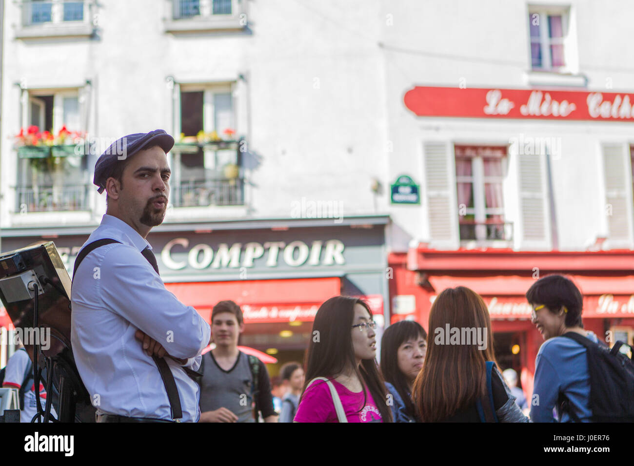 A waiter whistles as he takes a break from serving tourists at a cafe in the Montmartre neighborhood of Paris, France. - Stock Image