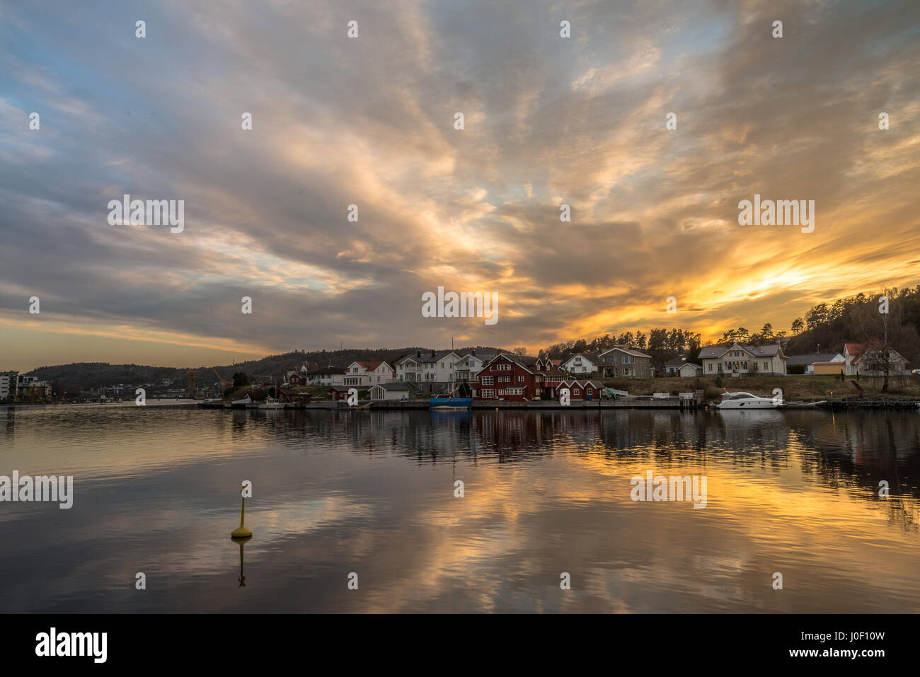 Sun setting over Porsgrunn city and river with an explosion of light - Norway - Stock Image