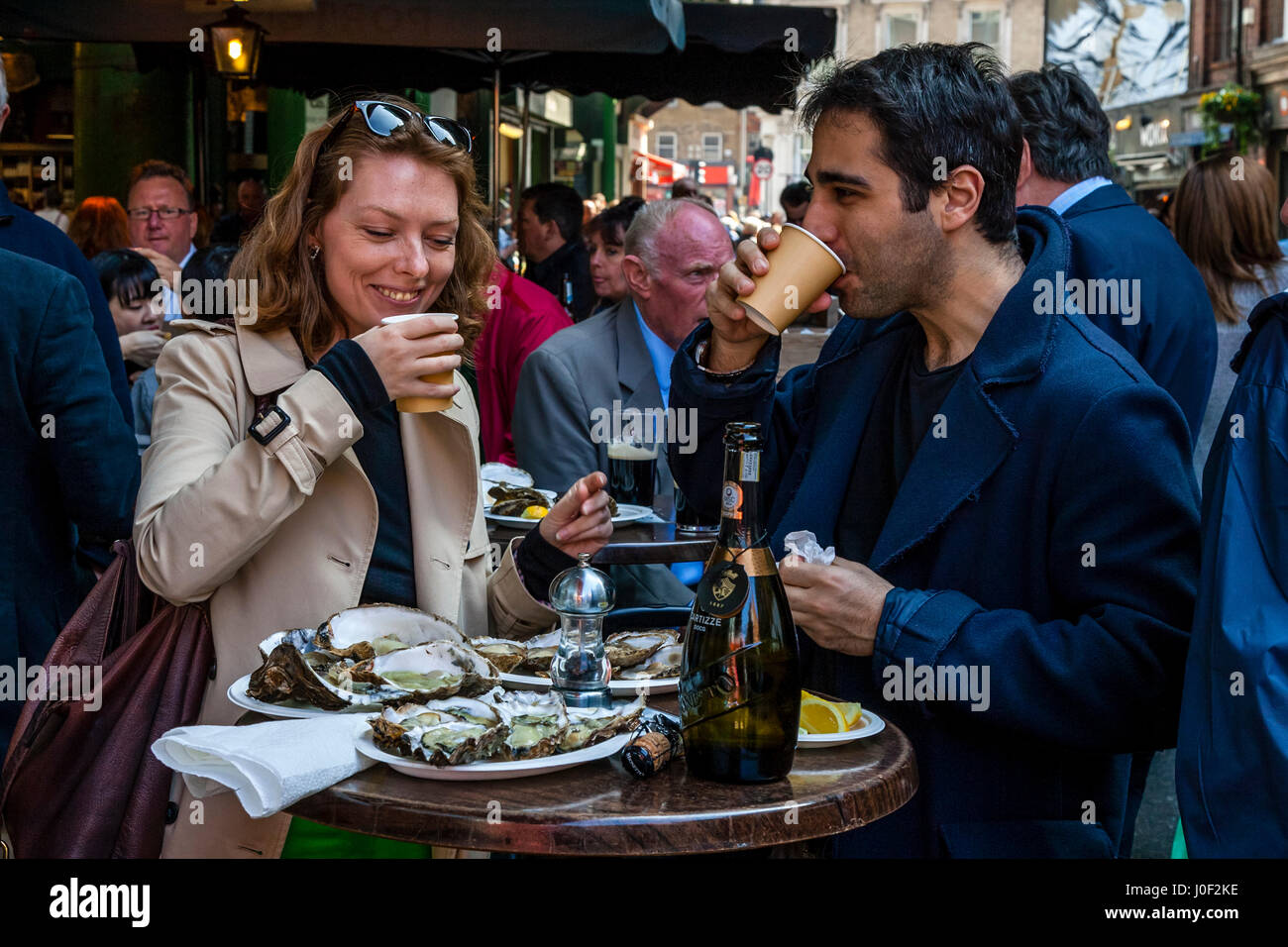 Two People Enjoying Prosecco and Oysters Outside A Restaurant In Borough Market, London, England - Stock Image