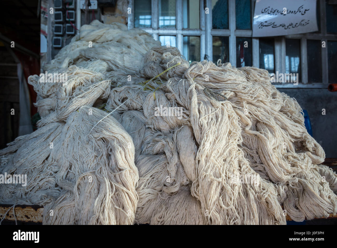 Wool yarns prepared for dyeing on the old Bazaar of Kashan city, capital of Kashan County in Iran - Stock Image