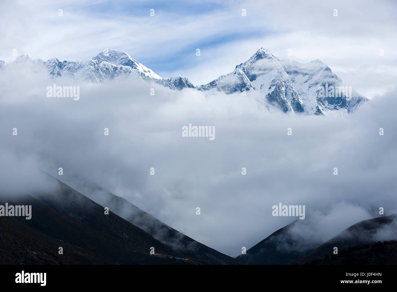Mount Everest and Lhotse rise above morning clouds, seen from Tengboche, Nepal. Photo © robertvansluis.com - Stock Image