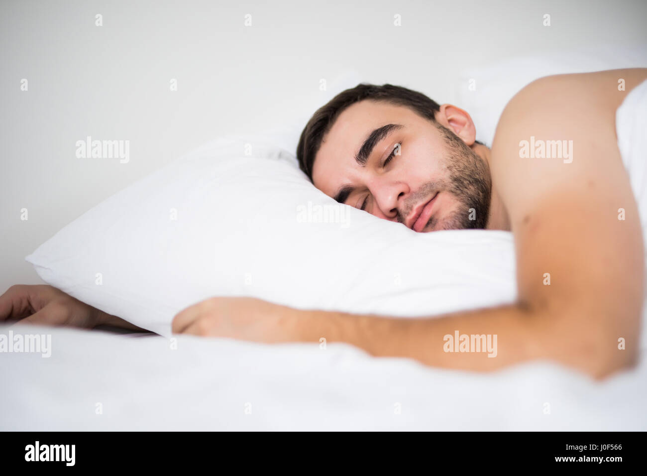 Handsome young man sleeping in white bedding - Stock Image