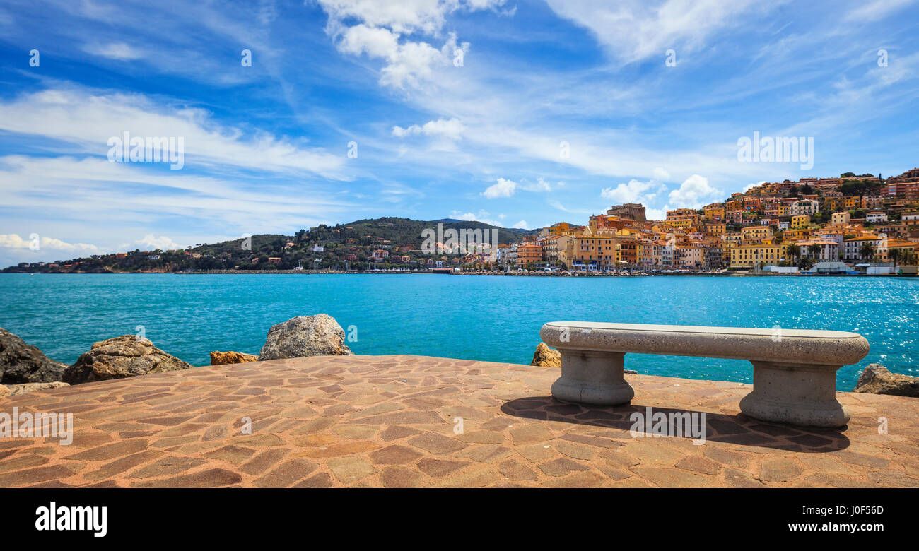 Bench on seafront in Porto Santo Stefano harbor, Monte Argentario, Tuscany, Italy. - Stock Image