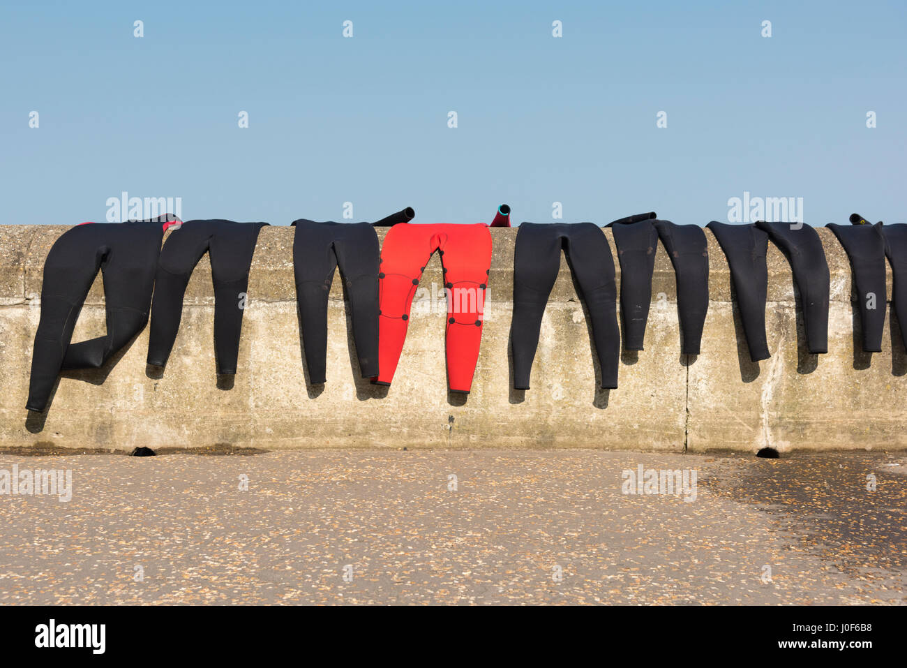 A line of black wetsuits drying on a wall with one red one. Difference. Odd one out. - Stock Image