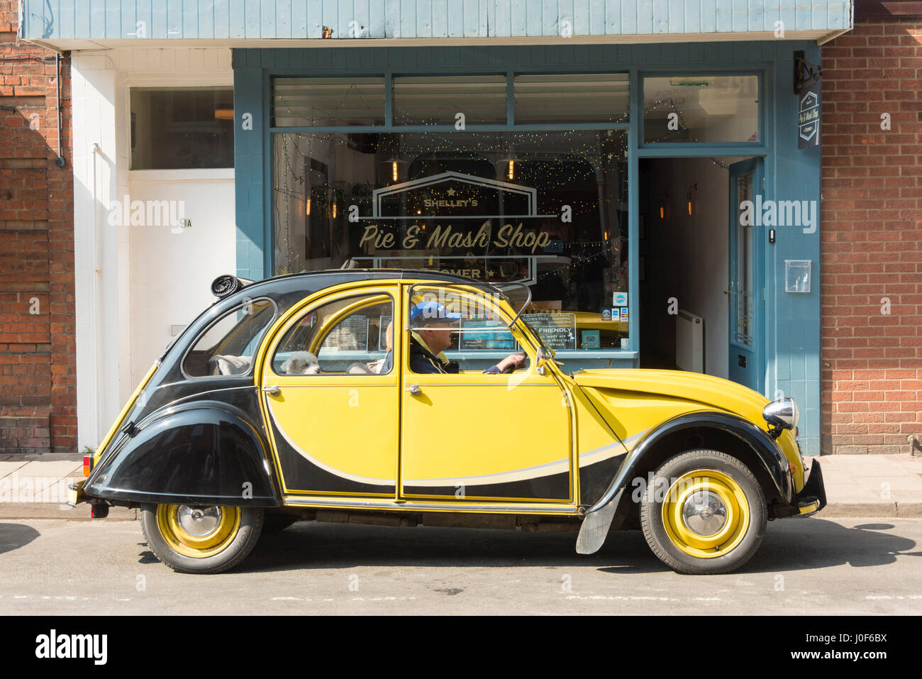 A black and yellow Citroen 2CV vintage car parked outside a pie and mash shop - Stock Image