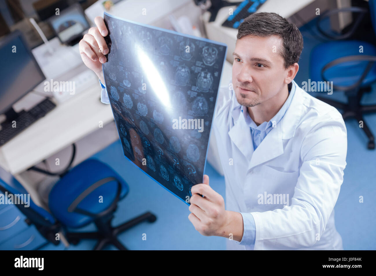 Handsome professional oncologist looking at the brain x ray images Stock Photo