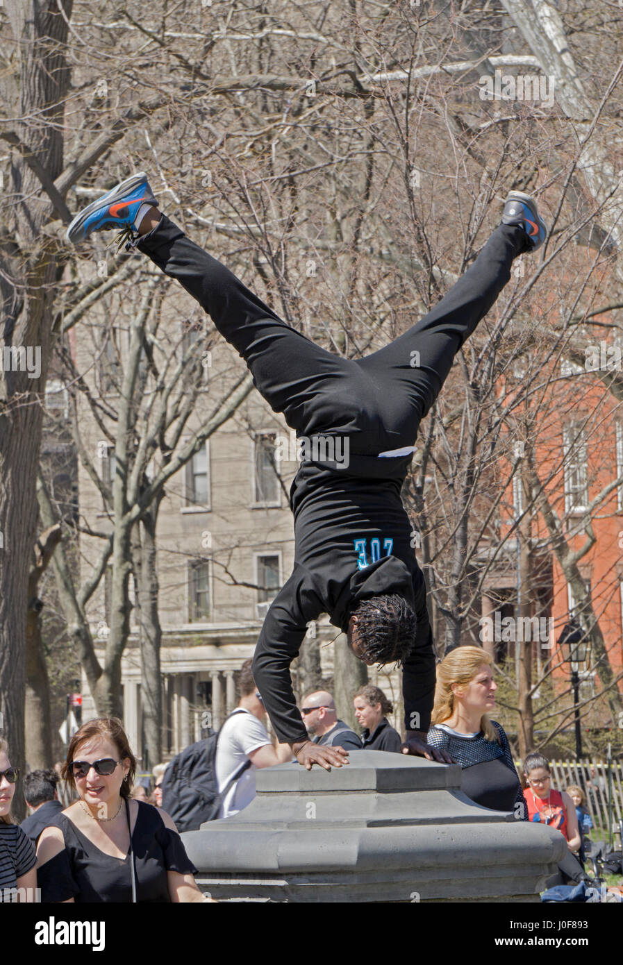 An acrobatic dancer performing a headstand near the fountain at Washington Square Park. His goup will solicit donations - Stock Image