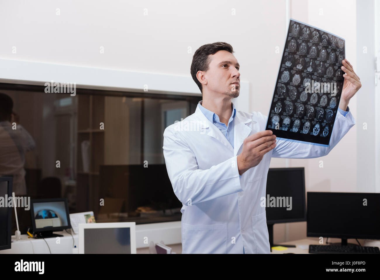 Handsome experienced radiologist looking at CT scan pictures - Stock Image