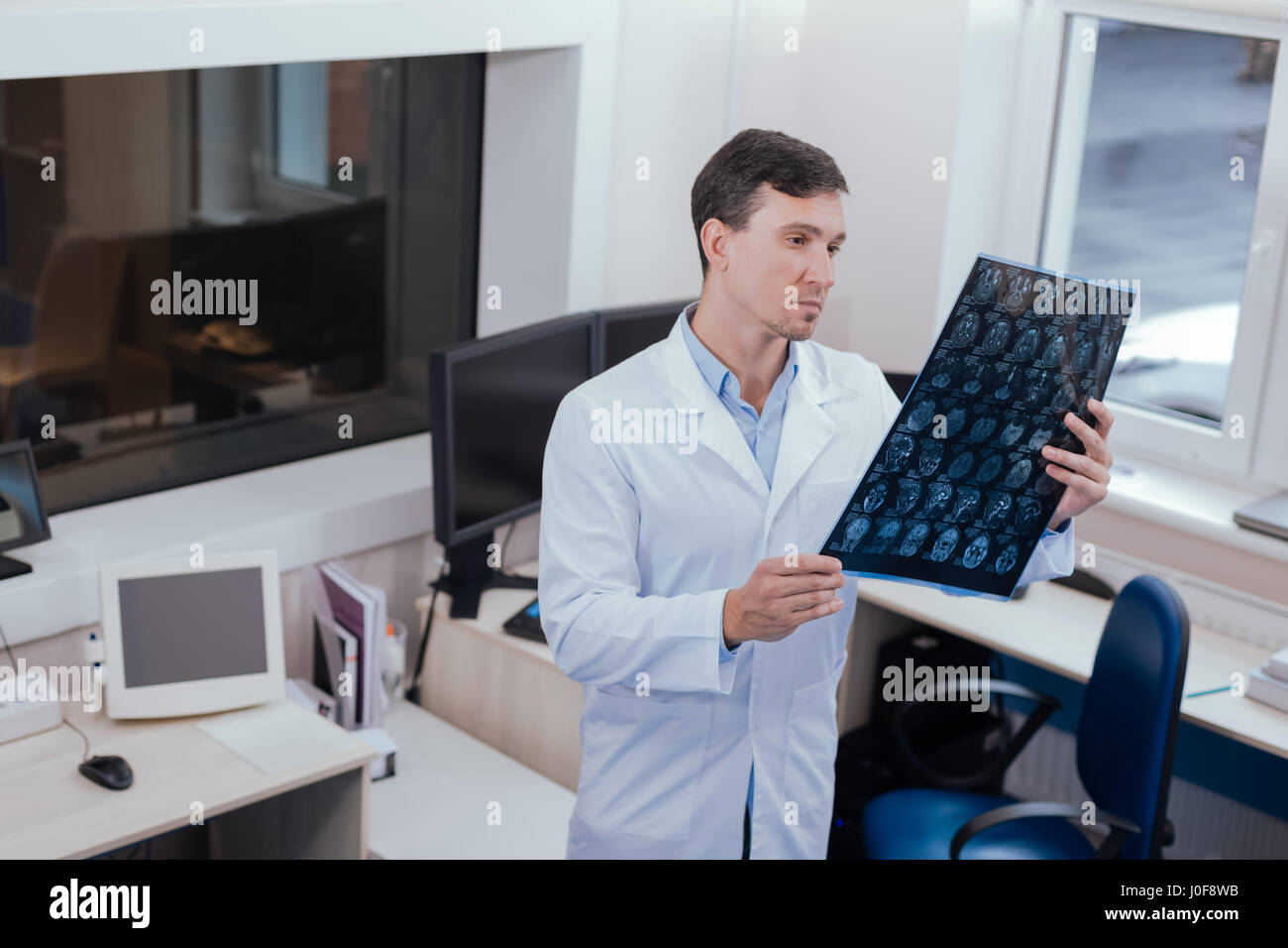 Serious male radiologist thinking about diagnosis - Stock Image