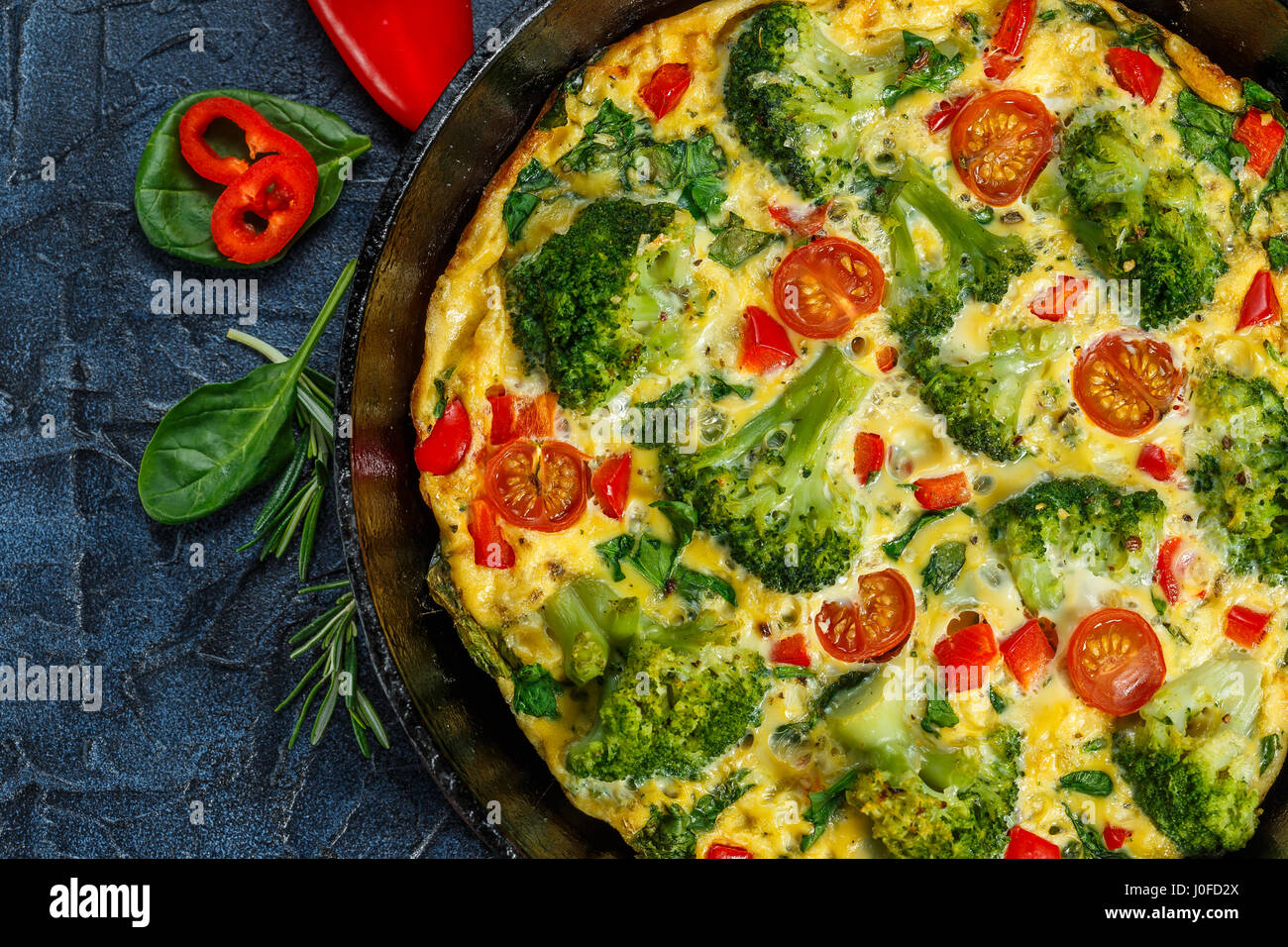 Frittata with broccoli, spinach, sweet peppers and tomatoes in iron skillet. Kind of Italian omelette with vegetables. - Stock Image