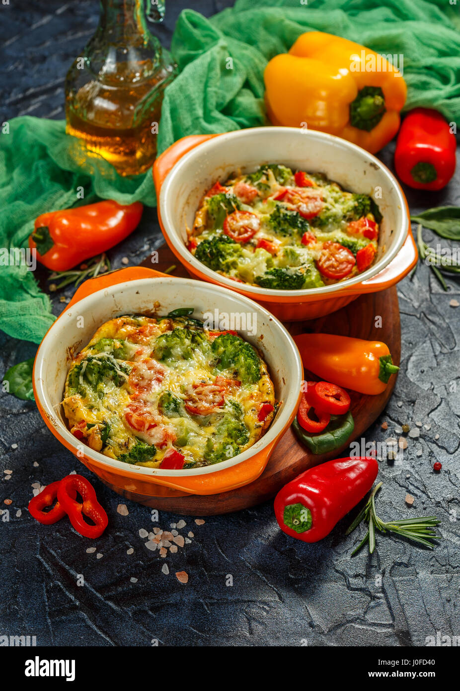 Frittata with broccoli, spinach, sweet peppers and tomatoes in two ceramic forms for baking. Italian omelet with - Stock Image