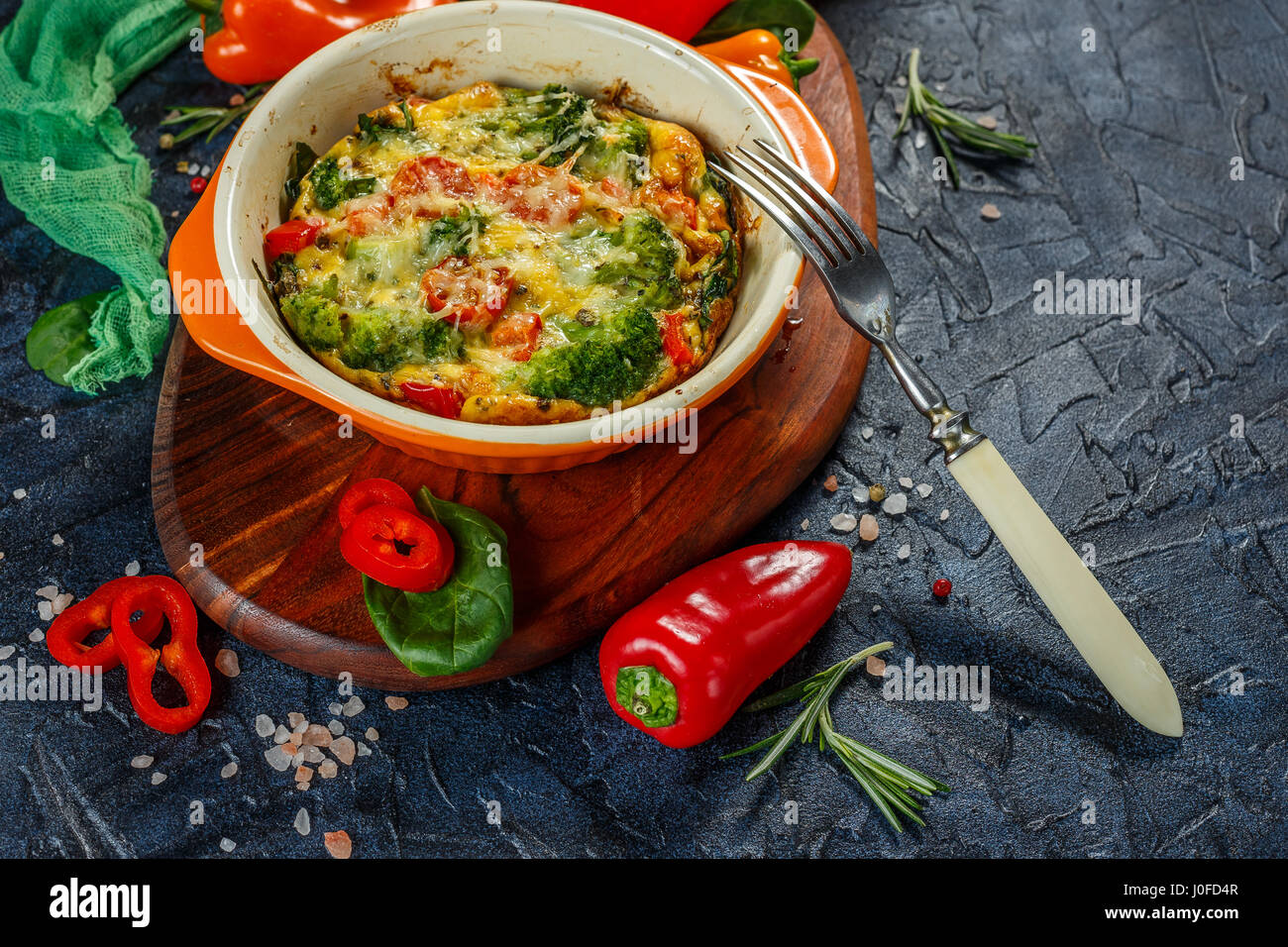 Frittata with broccoli, spinach, sweet peppers and tomatoes in ceramic baking dish. Italian omelet with vegetables. - Stock Image