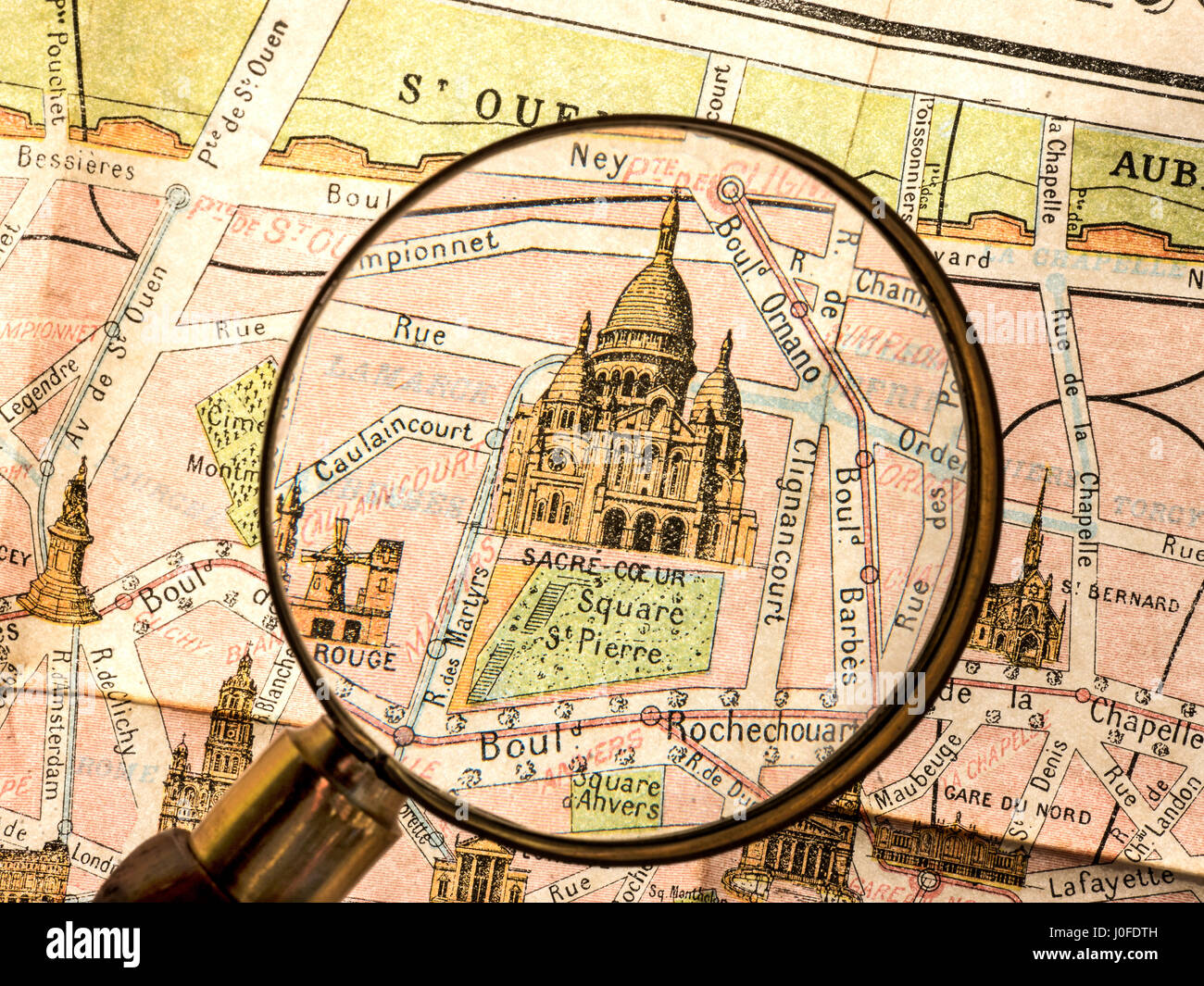 Magnifying Glass on detail of vintage retro Monumental Map of 1900's Paris, featuring Sacre Coeur Basilica Montmartre - Stock Image