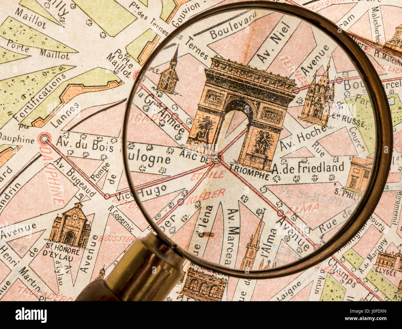 Magnifying Glass on detail of antiquarian vintage retro Monumental Map of 1900's Paris, featuring Arc de Triomphe - Stock Image