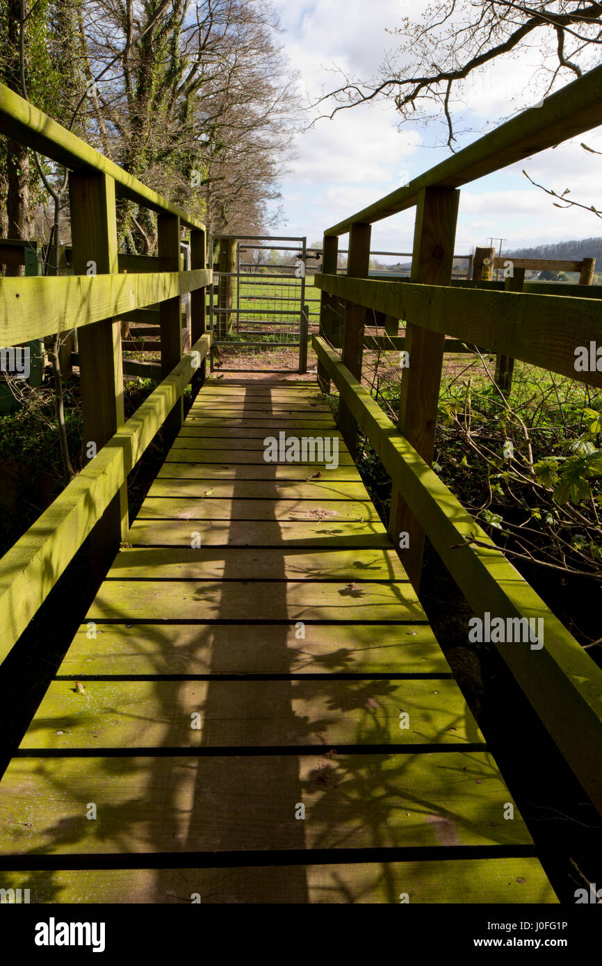 Modern footbridge on path crossing a stream in Herefordshire. The path connects, Turnastone church with Poston Court. - Stock Image