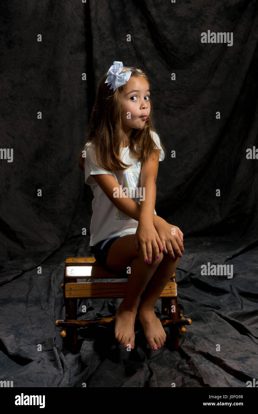 little girl modeling in studio brown background siting on a wood chair - Stock Image