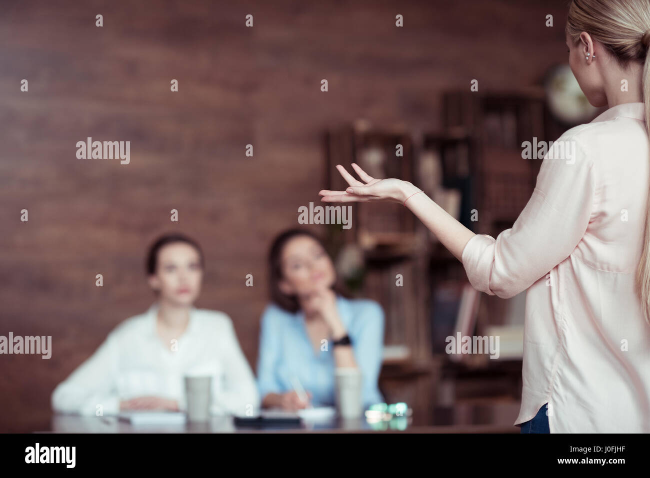 businesswoman gesturing and telling something to colleagues in office - Stock Image