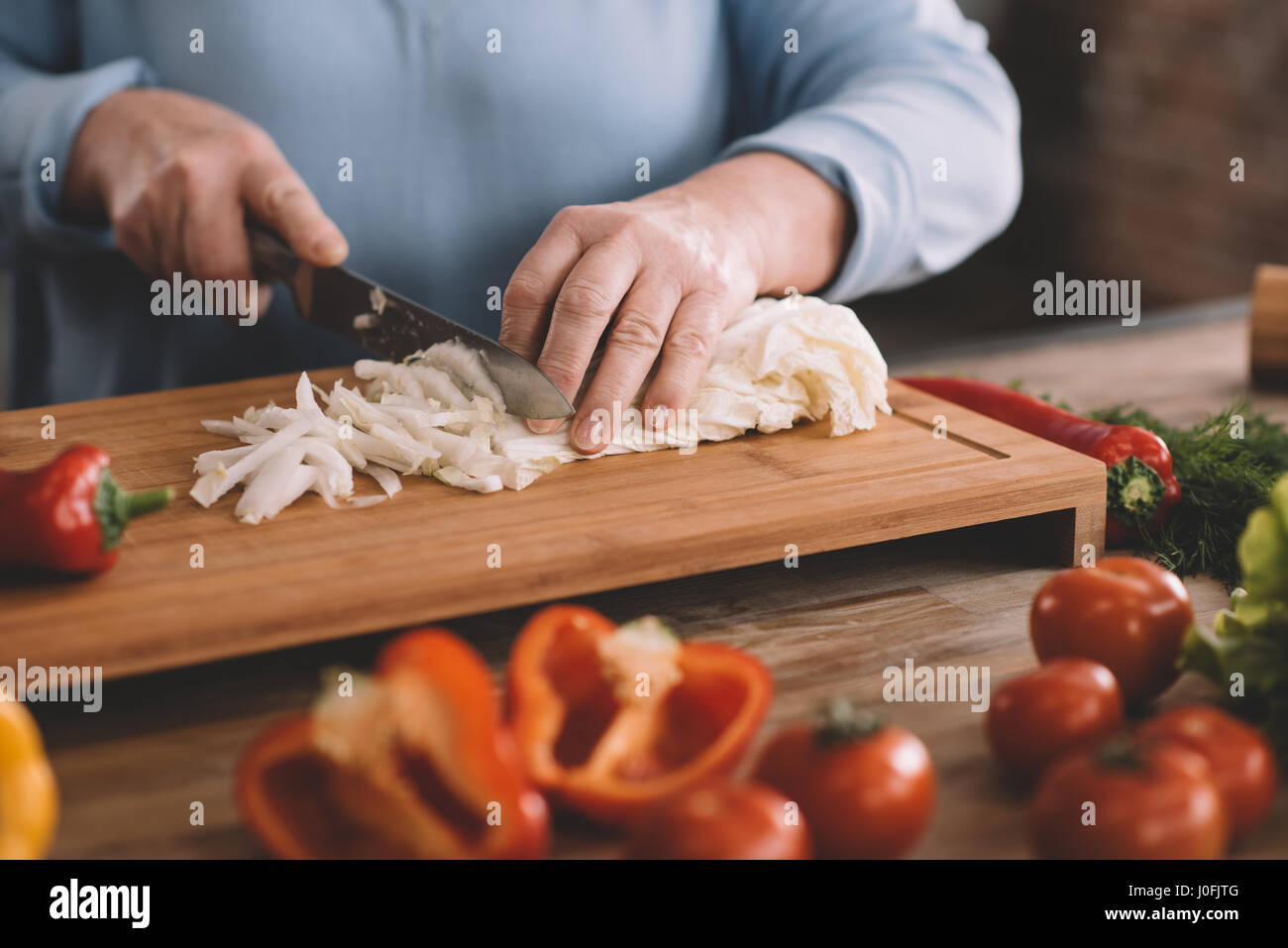 partial view of senior woman chopping onion for salad - Stock Image