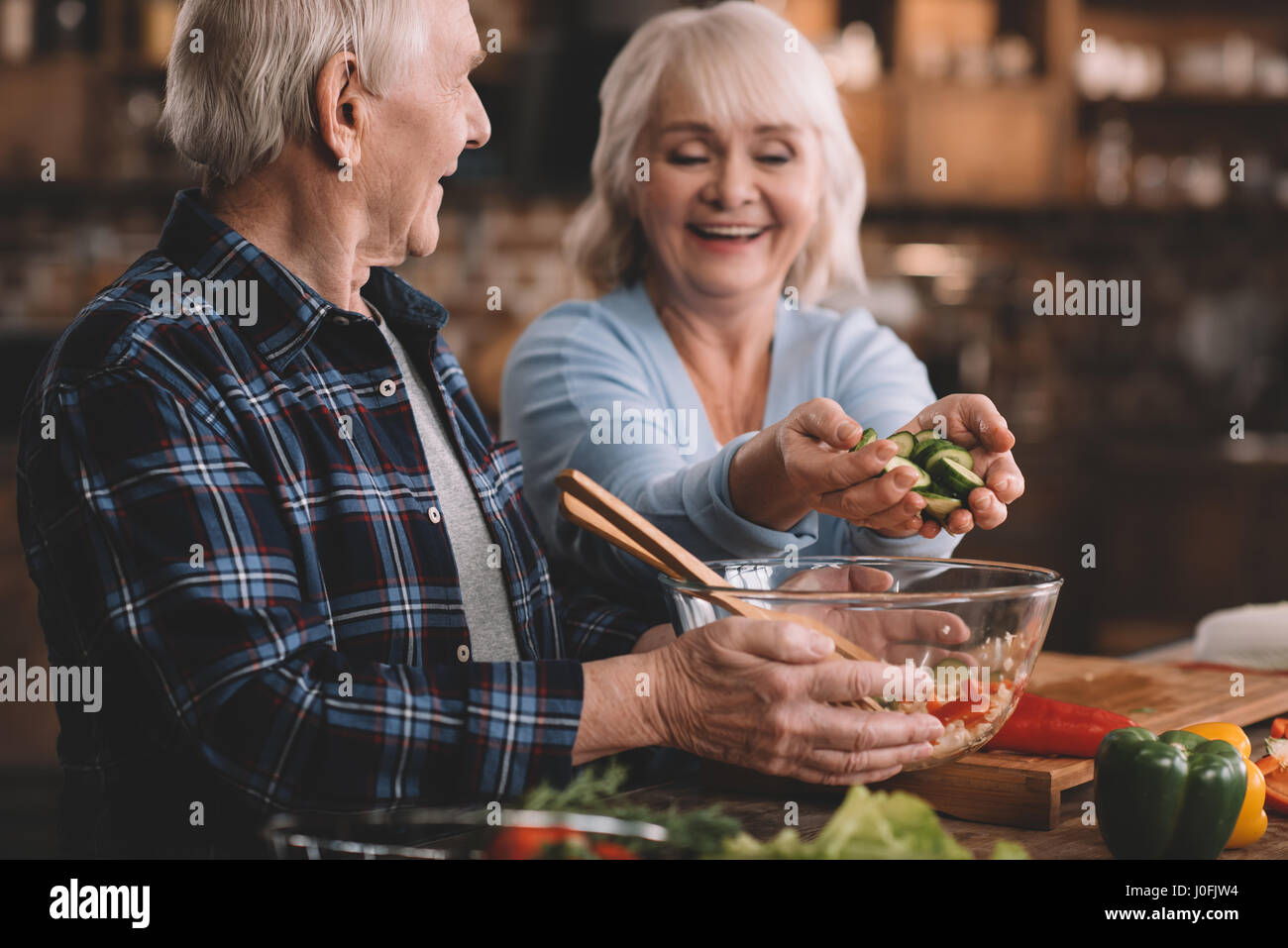 portrait of senior woman putting cucumbers into bowl in husband's hands - Stock Image