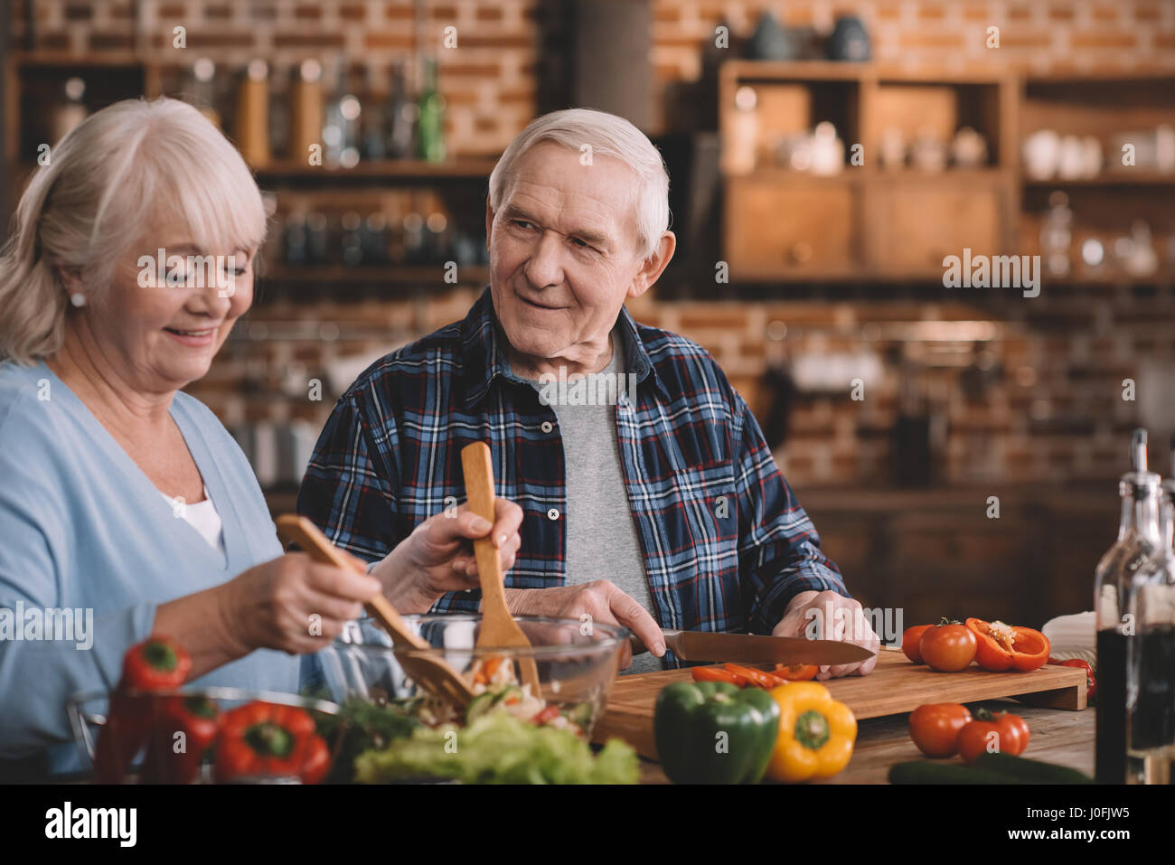 portrait of happy senior couple cooking together at home - Stock Image