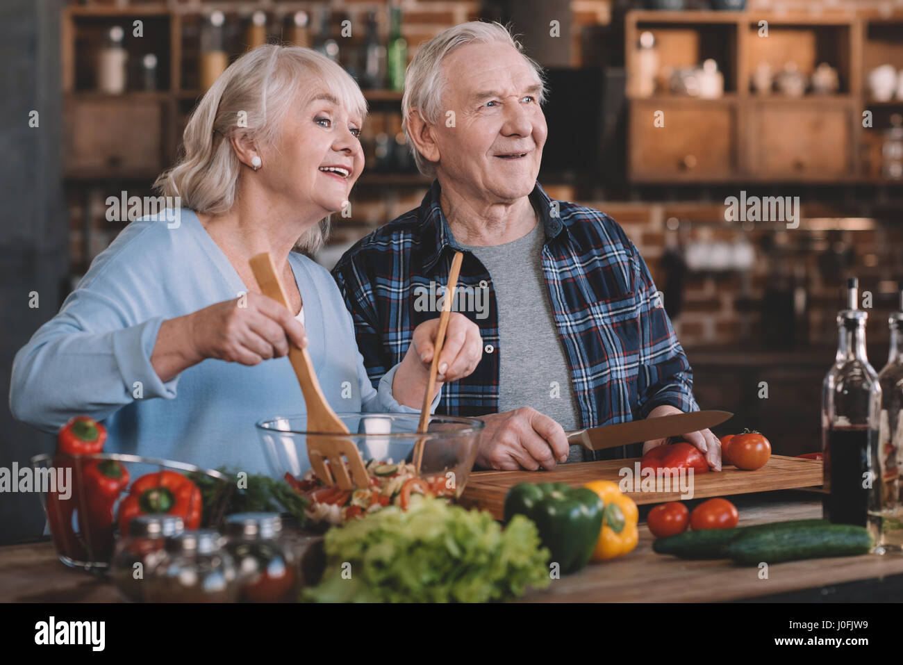 portrait of senior couple looking away while cooking together - Stock Image