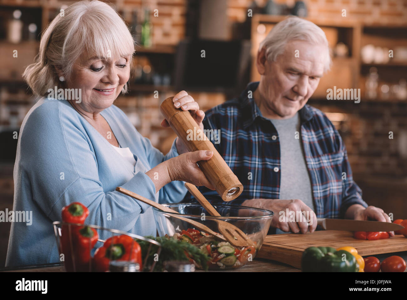 portrait of senior couple cooking together at home - Stock Image