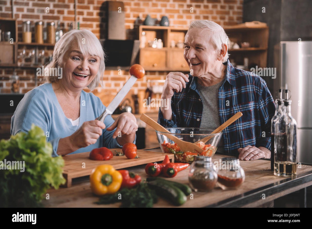 Happy senior couple cooking together and having fun at kitchen - Stock Image