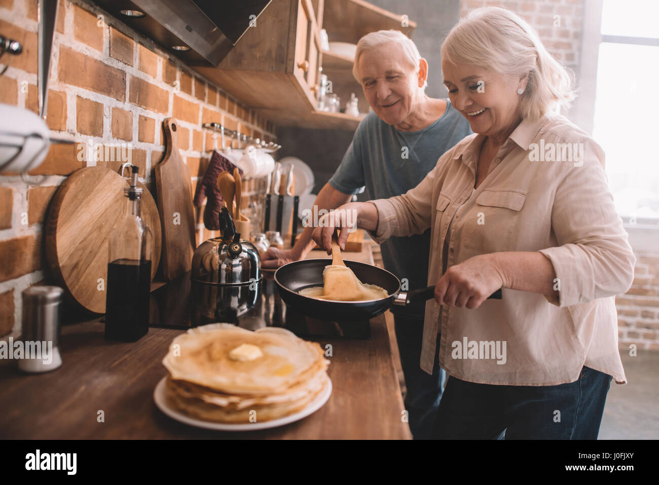 senior couple cooking pancakes on kitchen at home - Stock Image