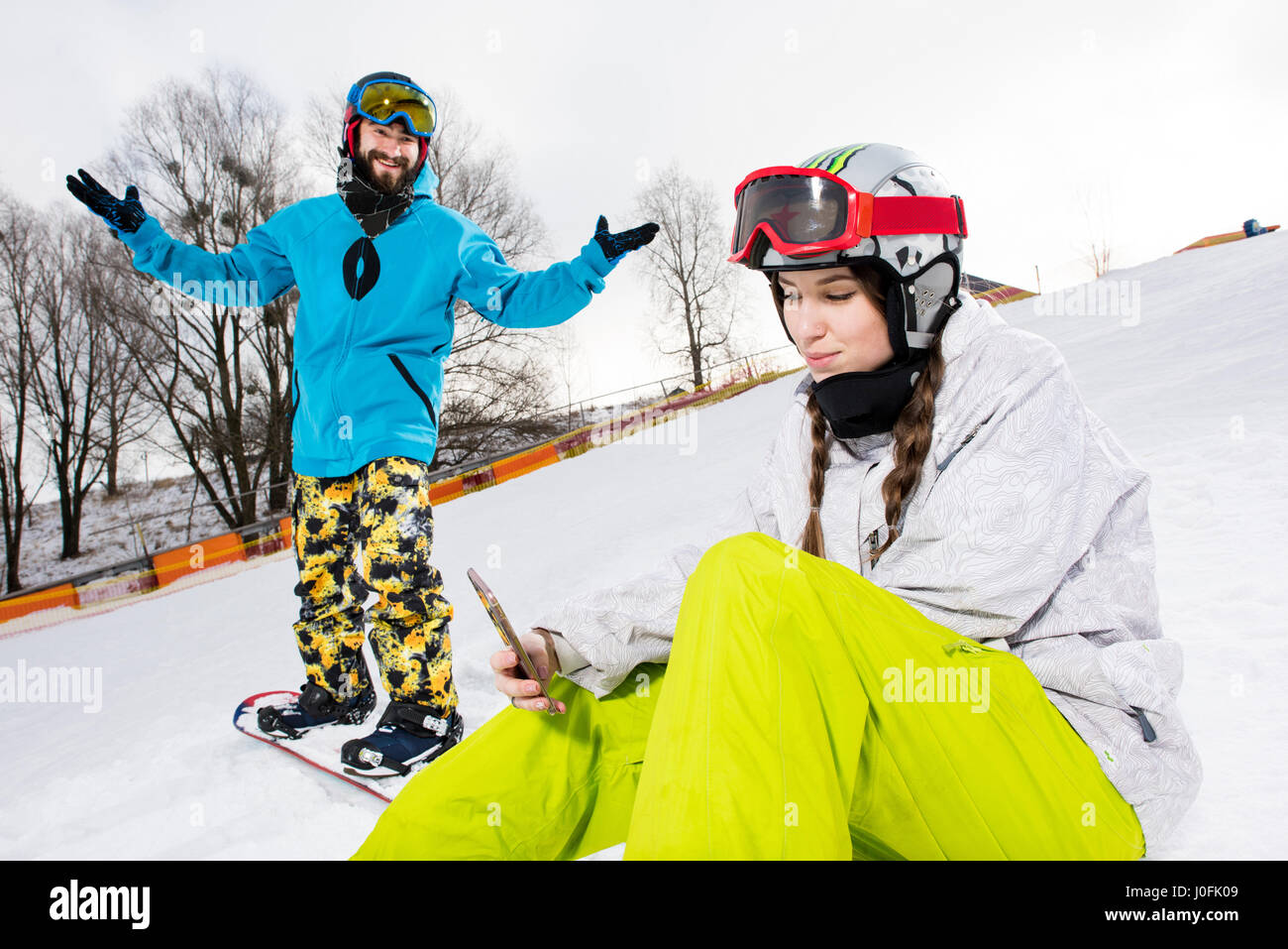 Happy bearded man on snowboard looking at female snowboarder using smartphone - Stock Image