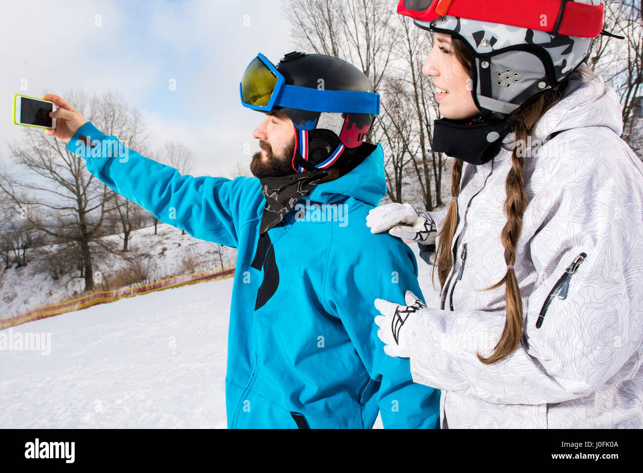 Young smiling couple of snowboarders taking selfie with smartphone - Stock Image