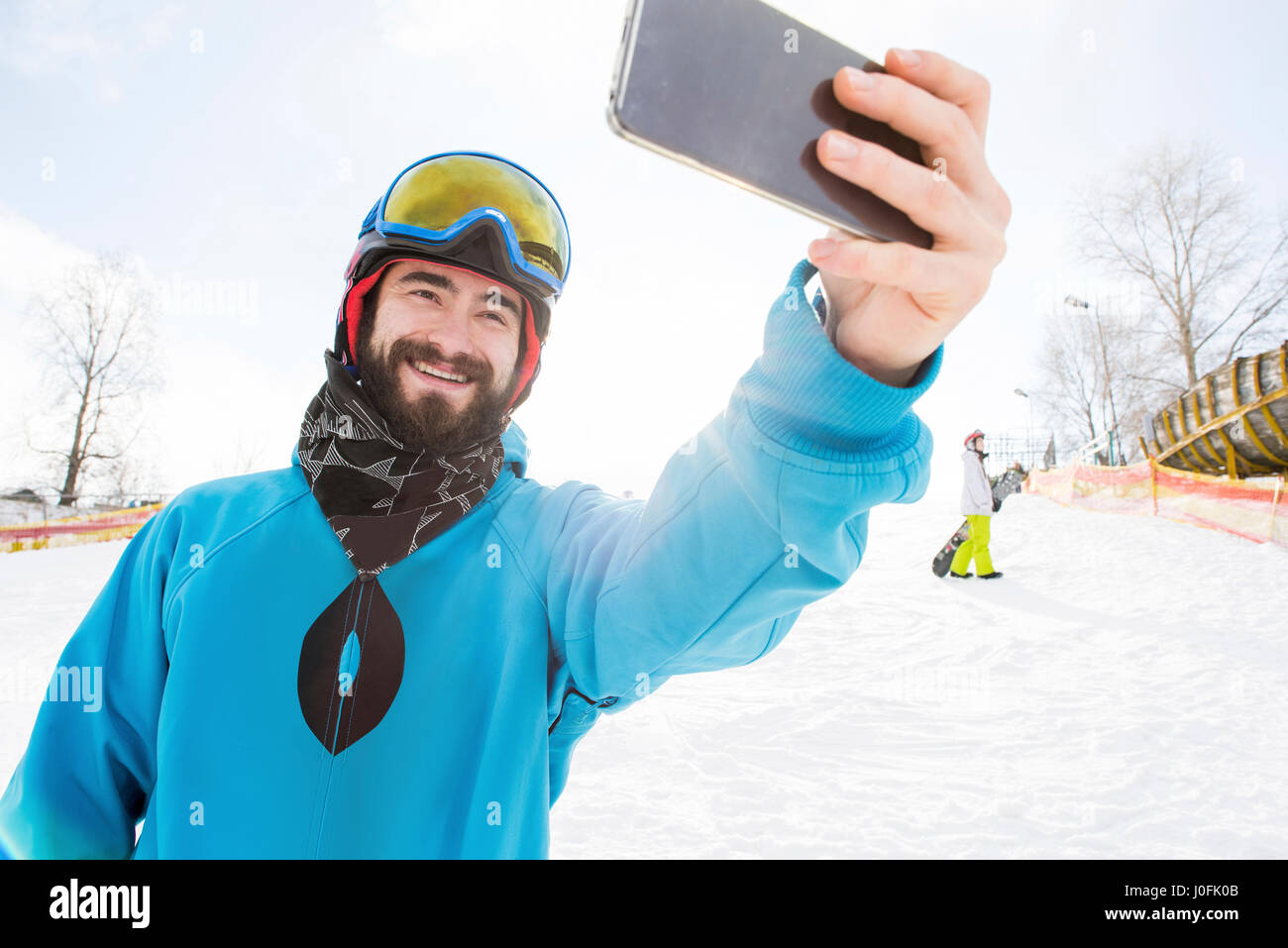 Young bearded male snowboarder taking selfie and smiling - Stock Image