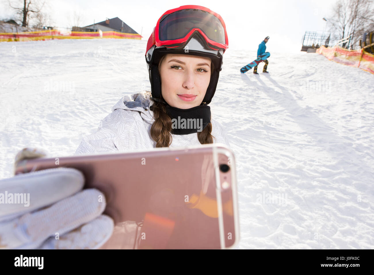 Beautiful young female snowboarder taking selfie with smartphone - Stock Image