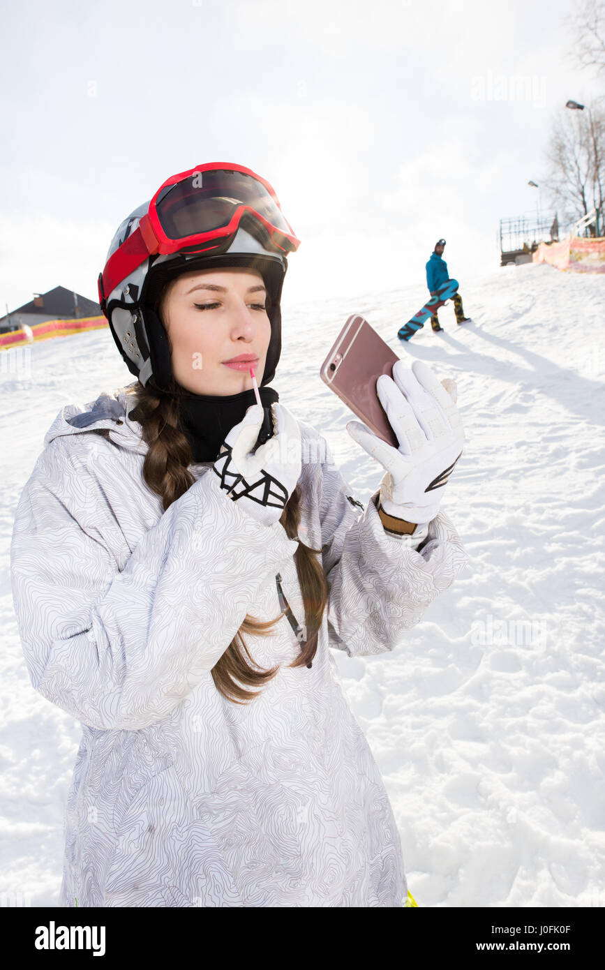 Attractive young female snowboarder applying lip gloss while looking at smartphone - Stock Image
