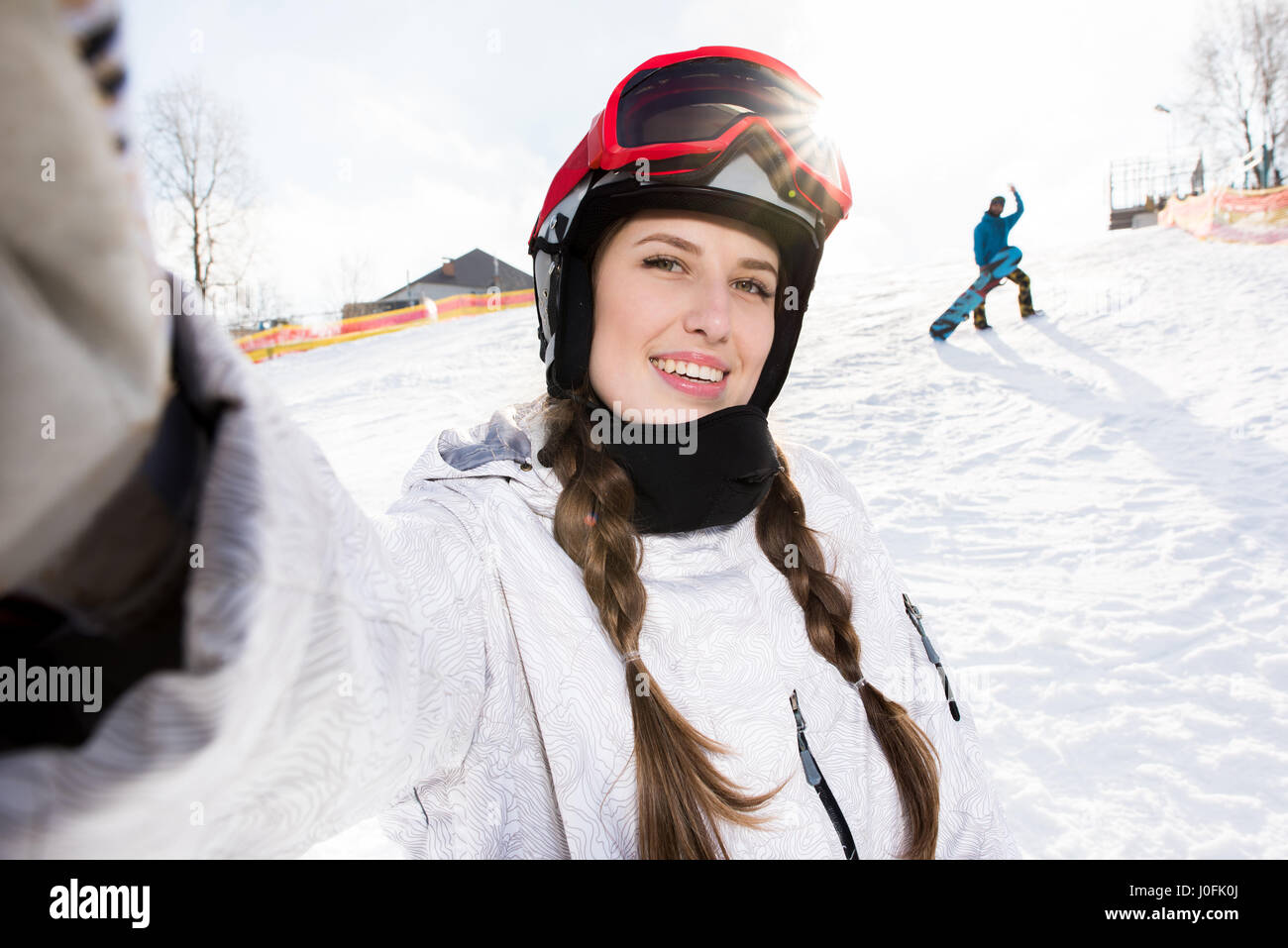 Beautiful smiling female snowboarder taking selfie at ski resort - Stock Image