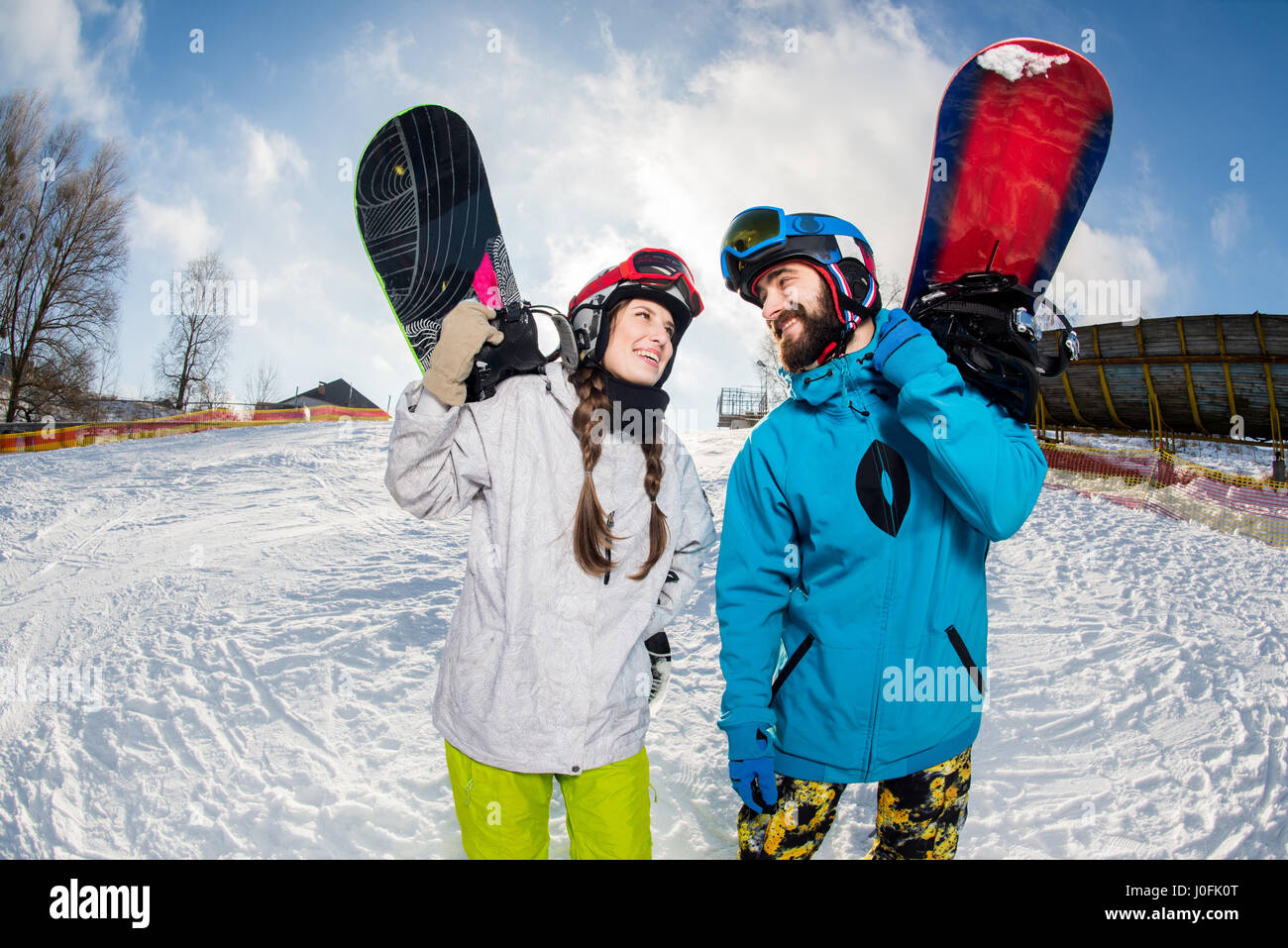 Young smiling man and woman holding snowboards and looking at each other - Stock Image