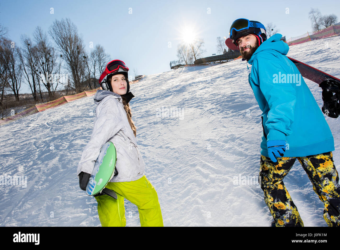 Young man and woman with snowboards walking up the hill and smiling - Stock Image