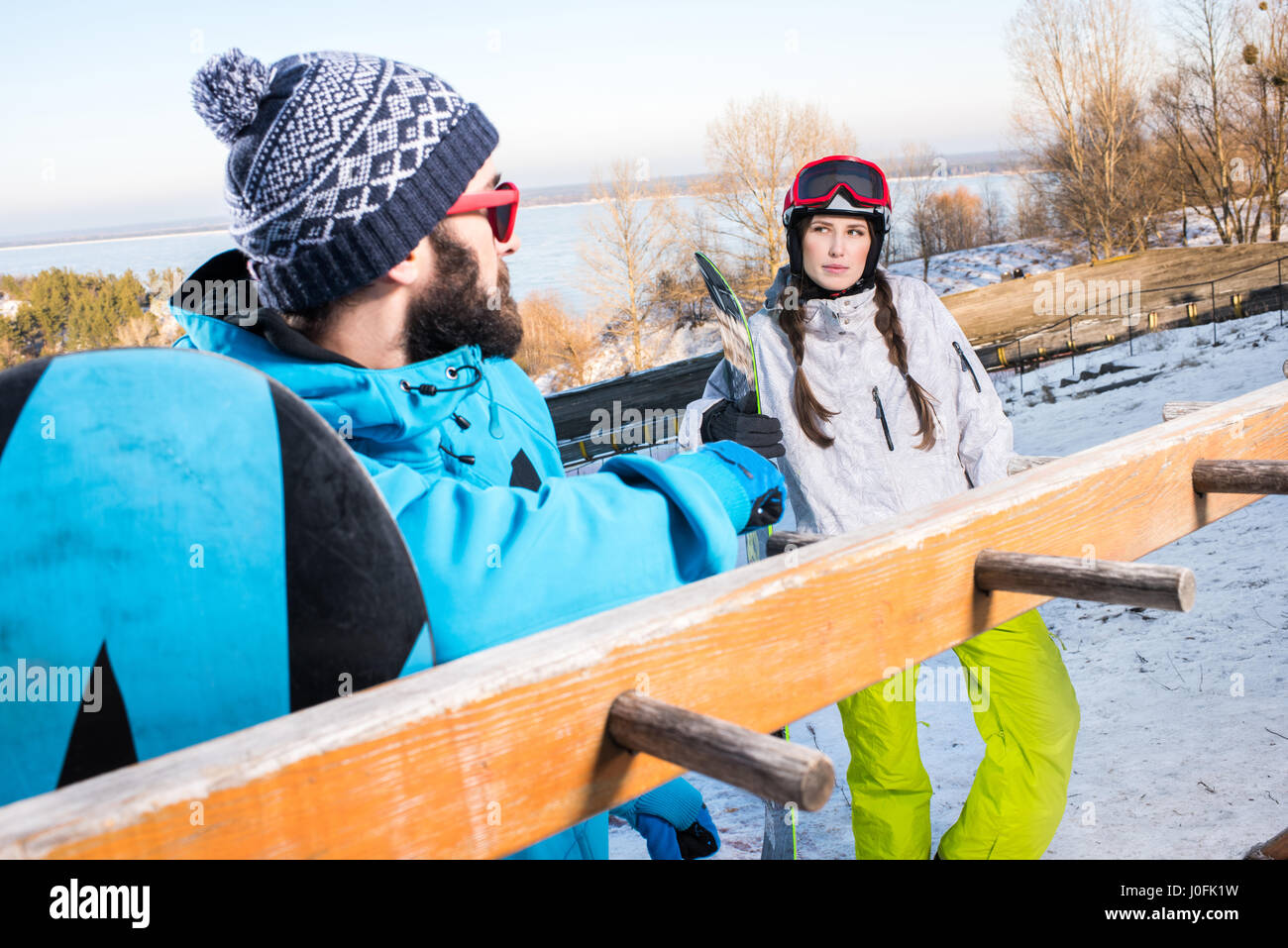 Young male and female snowboarders at ski resort  looking at each other - Stock Image