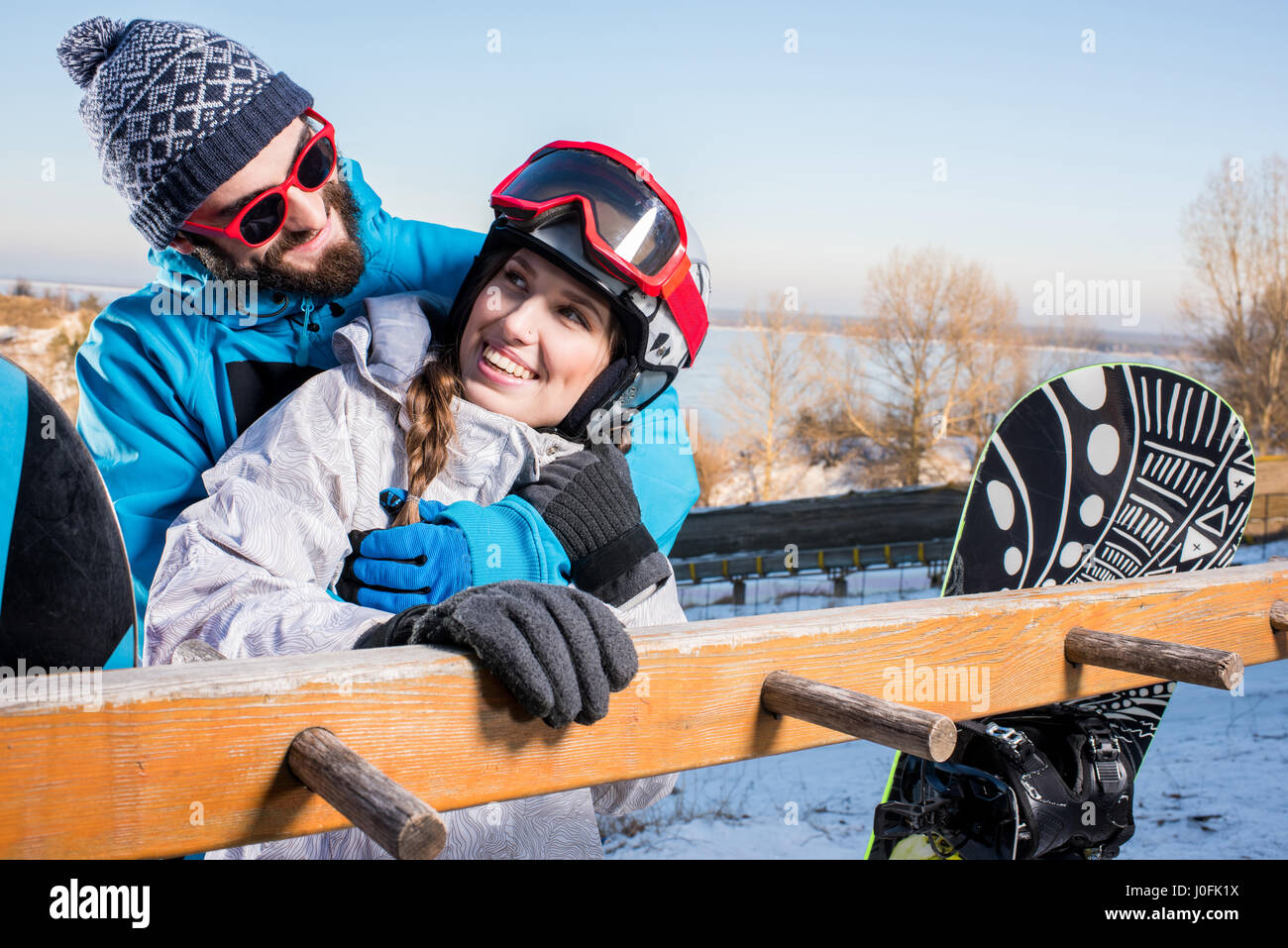 Young male and female snowboarders embracing and smiling at each other - Stock Image