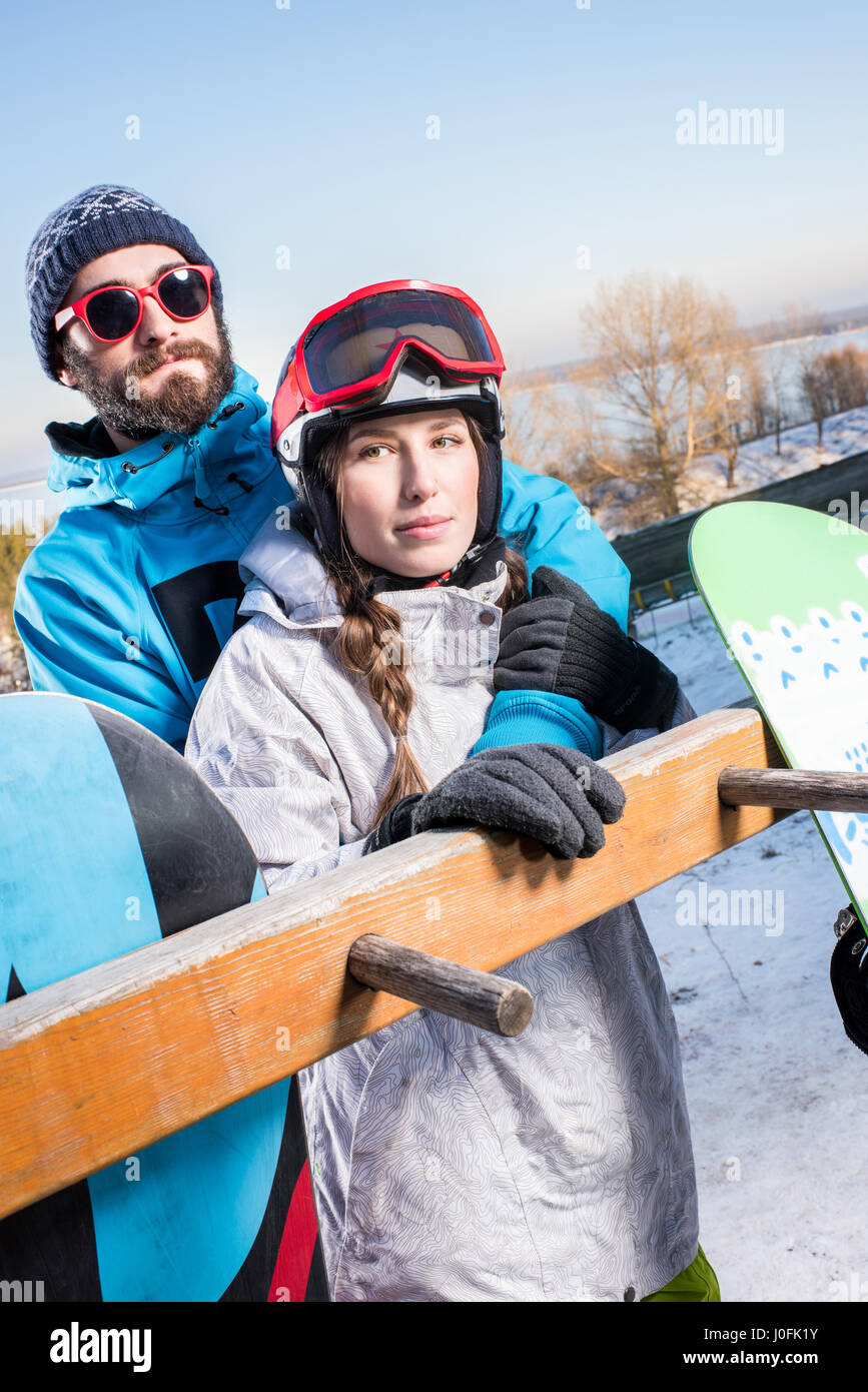 Young male and female snowboarders embracing and looking at camera - Stock Image