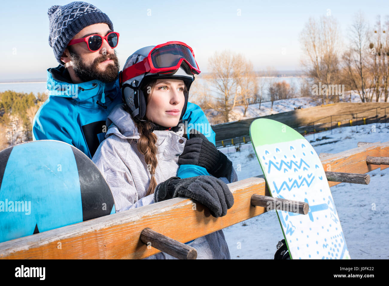 Young male and female snowboarders embracing and looking at distance - Stock Image