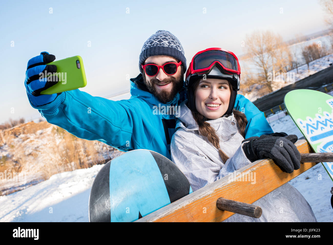 Young man and woman embracing and taking selfie with snowboars - Stock Image