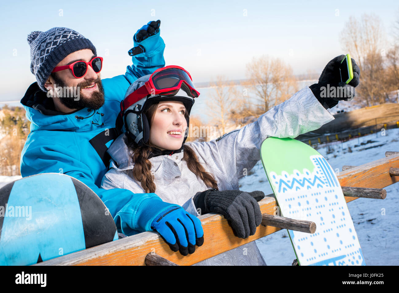 Young man and woman embracing and taking selfie with snowboards - Stock Image