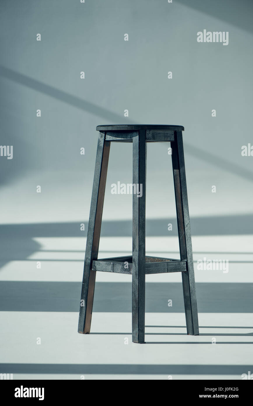 View of wooden bar stool with shadows on grey - Stock Image