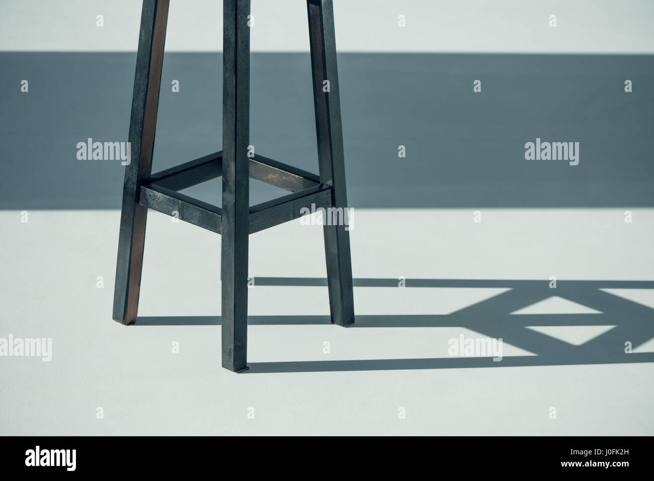 cropped shot of wooden bar stool and shadow on grey - Stock Image