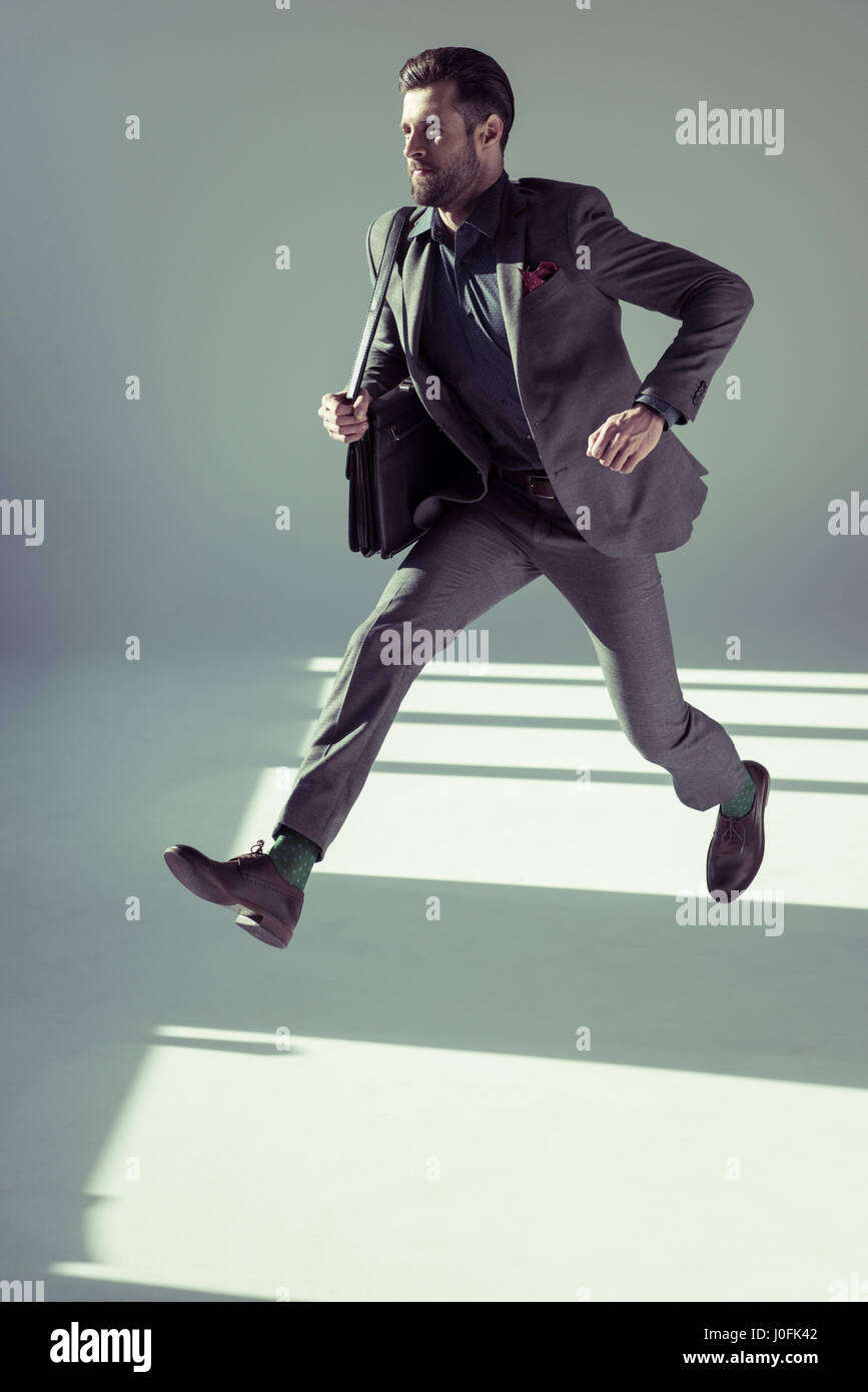 Handsome stylish businessman running with briefcase on grey - Stock Image