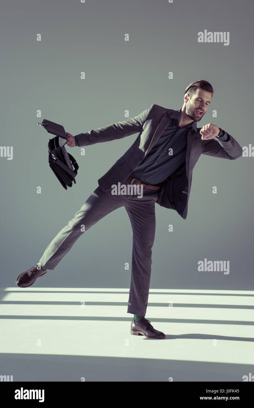 Handsome smiling businessman with briefcase looking at watch on grey - Stock Image