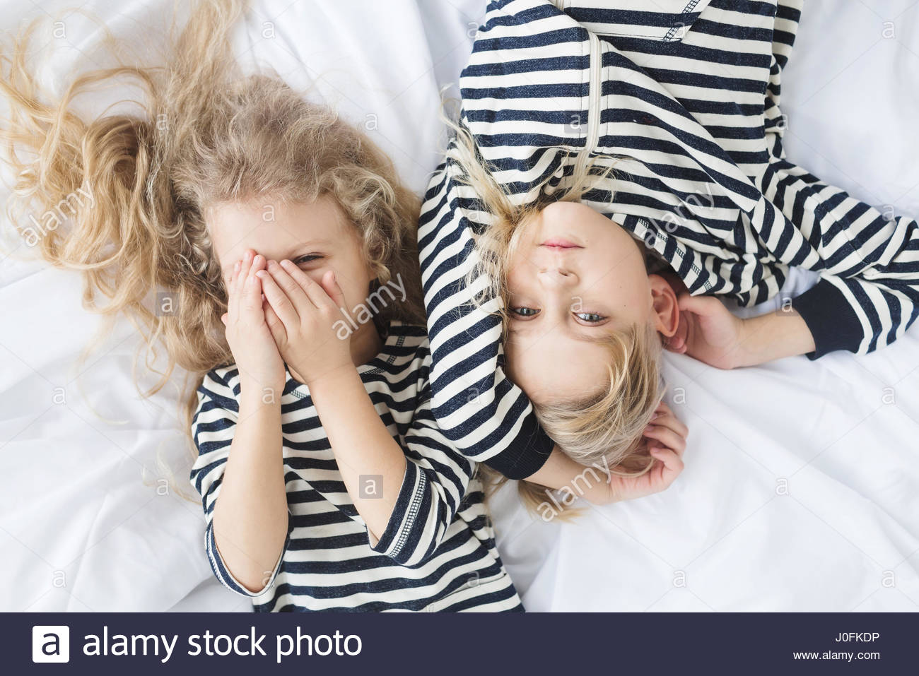 girl with white curly hair in a striped vest and a  boy with blond hair in a striped vest sleeping in bed. Children - Stock Image