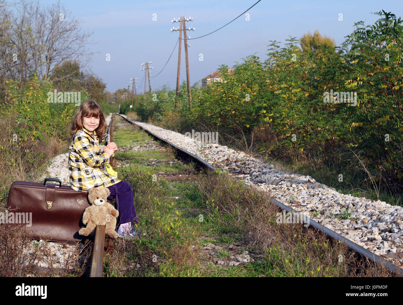 little girl sitting on suitcase and waiting for train Stock Photo